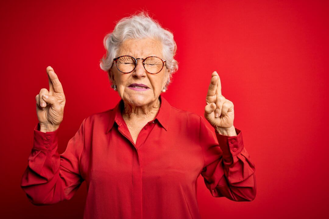 Senior beautiful grey-haired woman wearing casual shirt and glasses over red background gesturing finger crossed smiling with hope and eyes closed. Luck and superstitious concept.